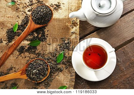 Still life with granulated tea and green leaves on wooden table, top view