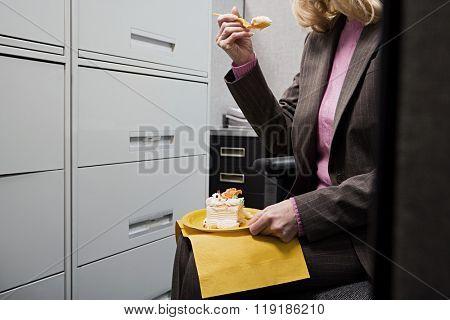 Businesswoman eating cake in secret