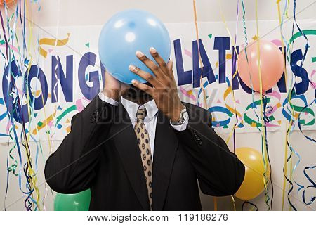 Businessman blowing up a balloon