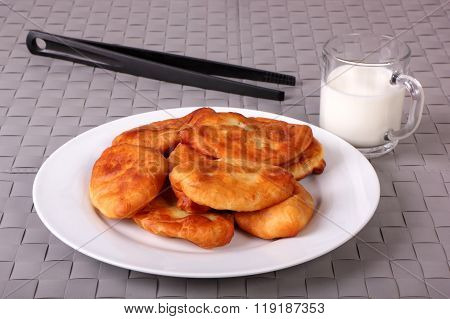 Fried Cakes On White Plate, Kitchen Tongs And Cup Of Milk