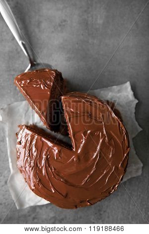 Chocolate cake with a cut piece and blade on gray background, closeup