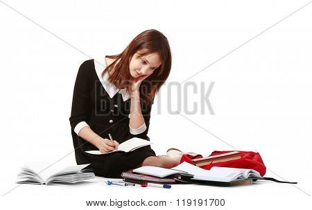 Beautiful schoolgirl with schoolbag writing in notebook isolated on white