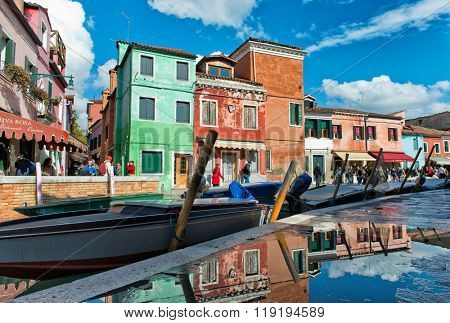 VENICE, ITALY - 17 OCTOBER 2015: Colorful houses with drying laundry hanging on the facades, Burano, Venice, Italy, painted in bright colors to guide the fishermen home in mist