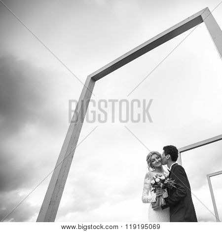 Happy Couple Of Newlyweds Hugging On A Roof Under Sky B&w