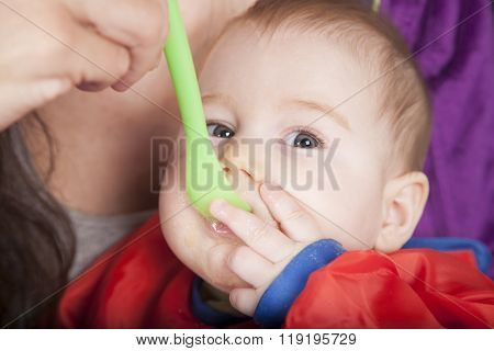 Hand Feeding In Green Plastic Spoon