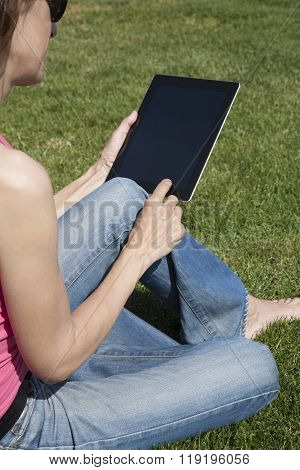 Tablet In Woman Hands On Grass