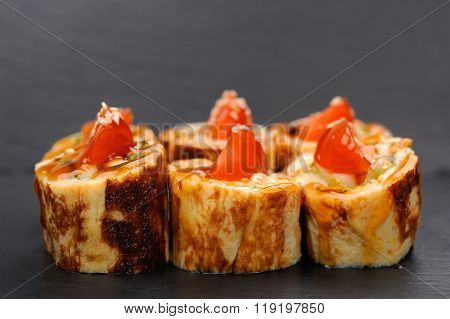 Set Of Yummy Japanese Rolls With Omelette And Tomatoes On Black Plate