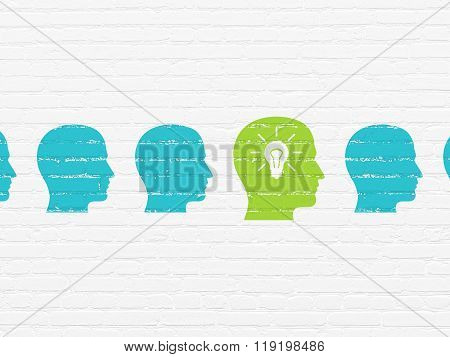 Business concept: head with light bulb icon on wall background