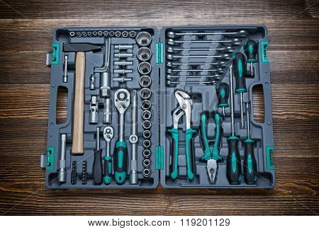 Open toolbox with different instruments on wooden workbench