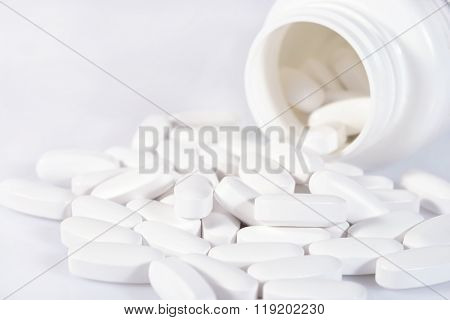 White Pills Spill Out From Bottle On A White