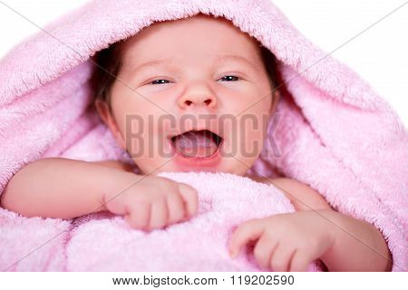 Close-up Portrait Of Laughing Smiling Newborn Baby On A Pink Terry-cloth Towel