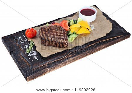 Beefsteak With Vegetables And Sauce On Wooden Plate, On White.