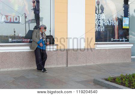 Elderly homeless man begging for some money near sport shop