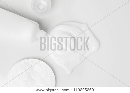 splash of white cream, tube and cosmetic cotton disk
