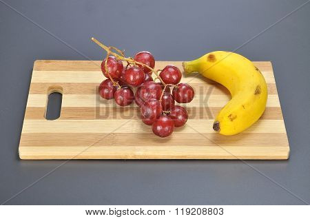 Delicious Bunch Red Seedless Crimson Grape And Banana On Bamboo Chopping Board
