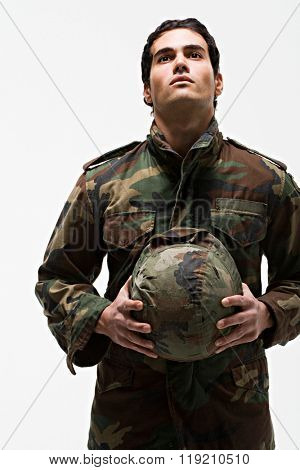 Young male soldier holding helmet