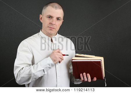 Man In The Bright Shirt Holding A Stack Of Books