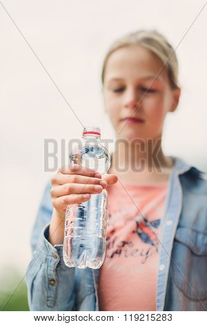 Girl drinking water outdoors - focus on bottle - very shallow depth of field