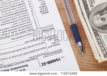 Us Tax Form With Pen, On Wooden Table Background