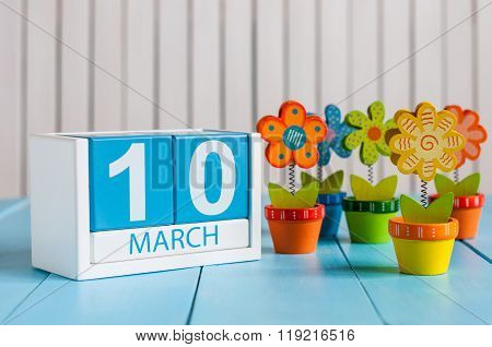 March 10th. Image of march 10 wooden color calendar with flower on white background.  Spring day, em