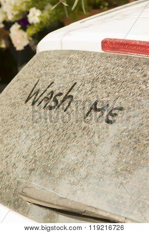 Wash me inscription on dirty car window