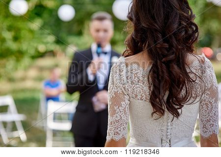 groom standing in front of the bride at a wedding ceremony
