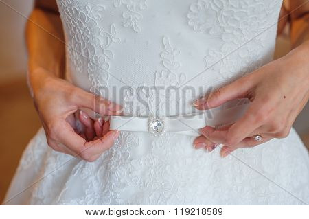 hands of bride on the belt with bow