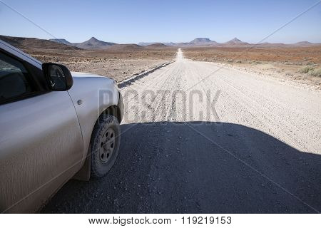 4x4 vehicle driving down a long gravel road