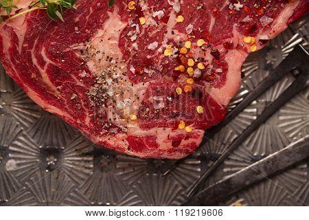 beef steak t-bone with vintage meat fork on metal backdrop