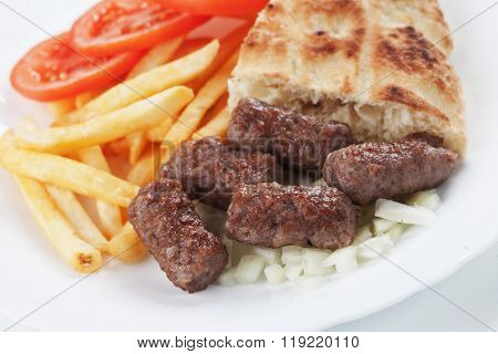 Cevapcici, bosnian minced meat kebab wit somun bread, onion and french fries