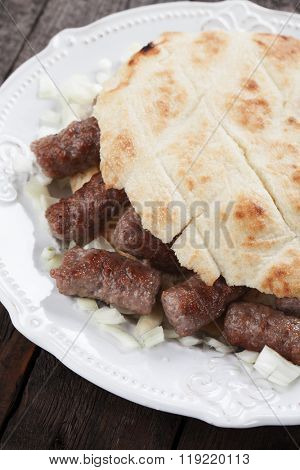 Cevapcici, bosnian minced meat kebab with onion and somun bread