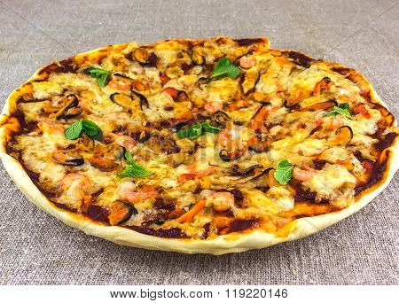 Homemade Pizza With Seafood On Linen Tablecloths  Adorned With Mint
