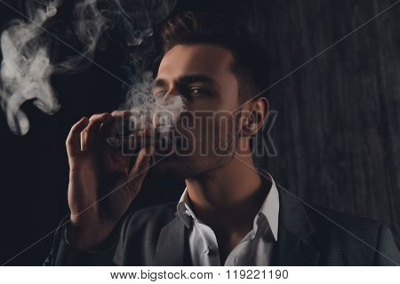 Cheeky Man In Suit On The Grey Background Smoking A Cigar