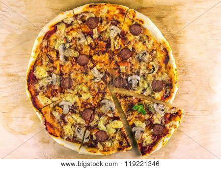 Freshly Baked Pizza With Salami, Mussels And Mushrooms, Fried Pieces On A Wooden Surface