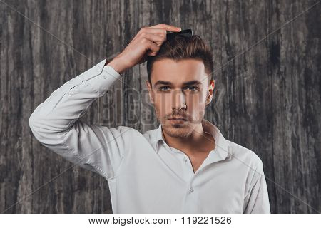 Confident Rigid Man Combing Hair On The Grey Background