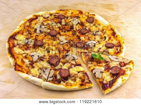Handmade Pizza With Salami, Mussels And Mushrooms, Fried Pieces On A Wooden Surface Decorated With F