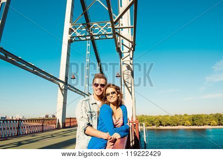 Cheerful Couple In Love Embracing Each Other On The Bridge