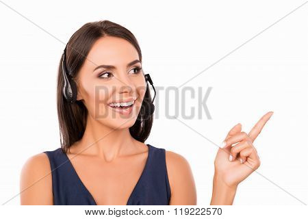 Cheerfull Assistant With Headset Smiling And Pointing With Finger