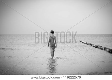 Bw Shot Of A Teenage Boy Who Is Walking Into The Sea
