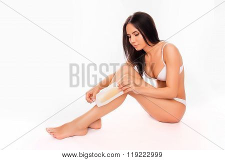 Young Pretty Woman Going To Shave Her Legs With Wax Stripe