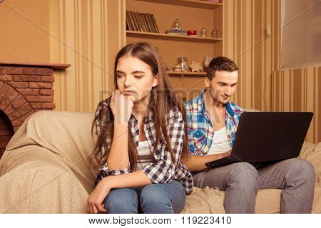 Cheerful Man Serfing Internet In Laptop Ignoring His Girlfriend