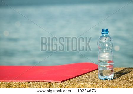 Pink Sport Mat And Water Bottle Outdoor On Sea Shore