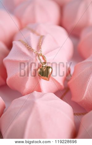 A Golden Heart Pendant On Pink Strawberry Meringues Background