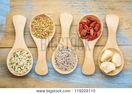 superfood abstract (hemp seeds, golden flax seeds, chiai seeds, goji berry, macadamaia nuts), top view of  wooden spoons
