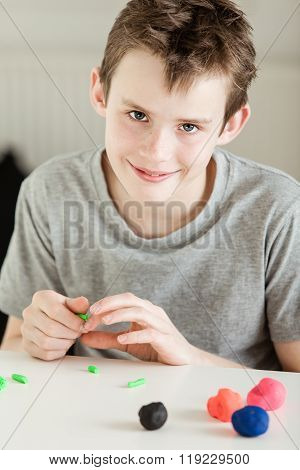 Smiling Boy Playing With Clay On Table