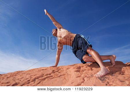 Young man doing yoga outdoors