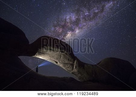 Spitzkoppe Rock arch with a person lighting the way to the stars