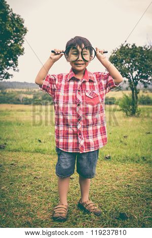 Full Body. Young Boy Exploring Nature With Magnifying Glass. Outdoors. Vintage Style.