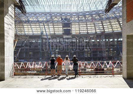 MOSCOW - AUG 08, 2015: Young people in helmets watching for the construction work of the main stadium Luzhniki, view from the back