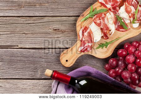 Prosciutto and mozzarella with red wine on wooden table. Top view with copy space